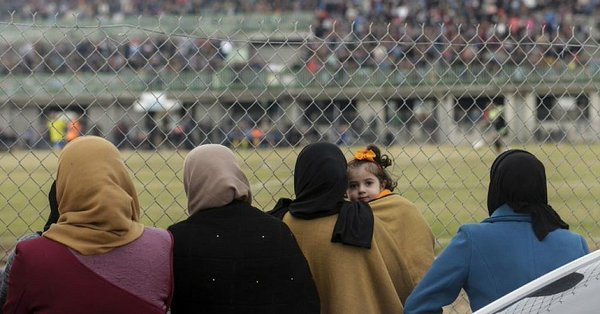 Women watch a soccer match from behind a chain link fence. (Courtesy of The Times of Israel)