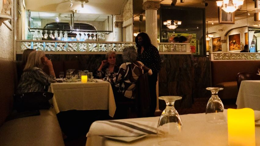 Oct. 3, 7:58 p.m. — Migliucci-Delfino takes a break from supervising to catch up with a table of her friends. (Courtesy of Cornelius Van Cott)